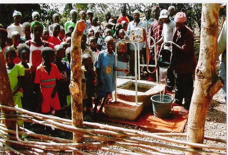 Schüler und Dorfbewohner freuen sich über das frische Wasser